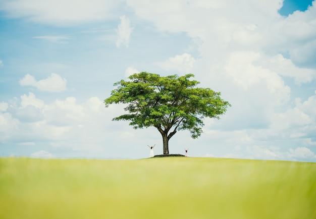 Aziatische familie die in vreugde in het park dichtbij grote boom springt