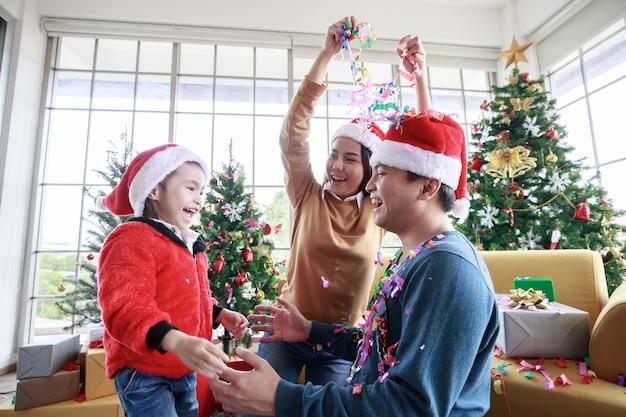 Aziatische familie die plezier heeft met kerstmutsen op de voorbank thuis en viert met kerstmis het papier en de geschenkdoos met kerstboom in de woonkamer. mijn vader en moeder happy voorin, samen met dierbaren.