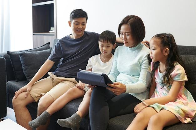 Aziatische familie die thuis op de bank rust en naar tekenfilms of films kijkt op tabletcomputer