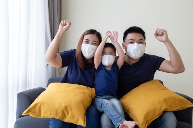 Aziatische familie dragen van beschermende medische masker voor het voorkomen van virus covid-19 en hand omhoog en zitten samen in de woonkamer. familiebescherming tegen verontreinigd luchtconcept