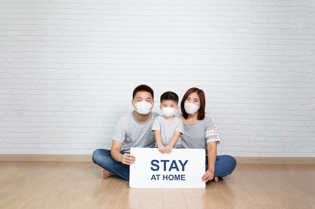 Aziatische familie dragen van beschermende medische masker voor het voorkomen van virus covid-19 met wit papier met thuis bij de hand en samen zitten op de vloer thuis