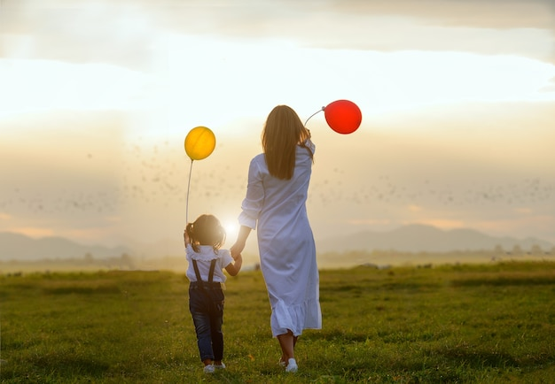 Aziatische familie. familie met ballonnen in de wei achter de zonsondergang. aziatische familie
