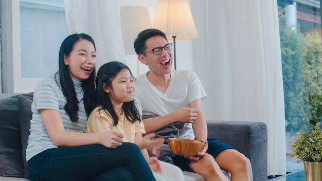 Aziatische familie geniet van hun vrije tijd ontspannen samen thuis. lifestyle vader, moeder en dochter kijken 's nachts samen tv in de woonkamer in een modern huis.