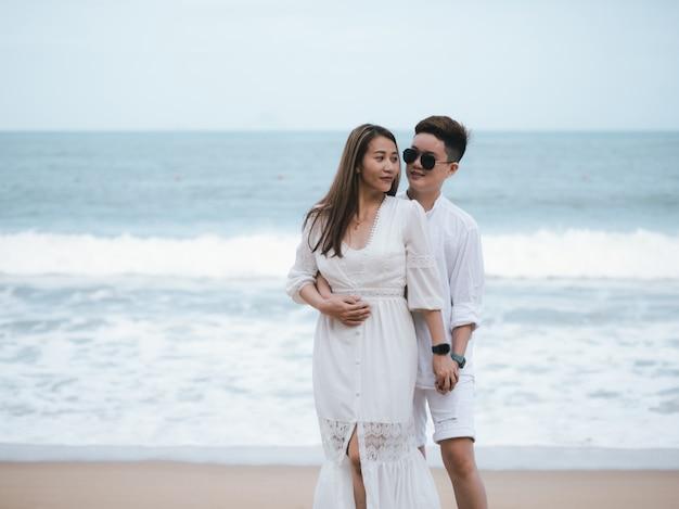 Aziatische familie in witte kleren in de buurt van de oceaan