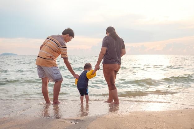 Aziatische familie met 2 jaar oud de jongenskind die van de peuterbaby blootvoets op het strand in water bij zonsondergang lopen.