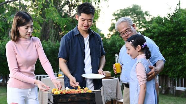 Aziatische familie met een barbecuefeestje thuis. gegrilde bbq koken voor het diner in de achtertuin. levensstijl op zomervakantie.