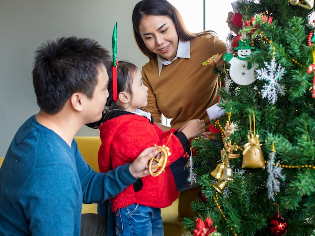 Aziatische familie met ouder en kind-dochter die de kerstboom versiert, voelt zich gelukkig en leuk. in concept gezinsactiviteit van december tot januari met prettige kerstdagen en een gelukkig nieuwjaar.