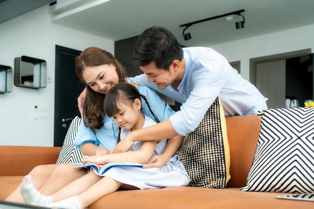 Aziatische familie met vader, moeder en haar dochter die het boek van het sprookjesverhaal op bank thuis lezen