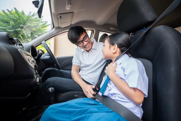 Aziatische familie met vader probeert de veiligheidsgordel van haar kleuterschooldochter klaar te maken om naar de chauffeur te gaan en gaat 's ochtends naar school.