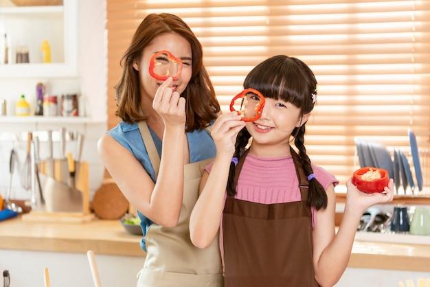 Aziatische familie, moeder en dochter genieten van koken en bereiden samen salades in de keukenkamer thuis.