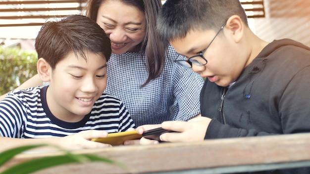 Aziatische familie moeder en zoon kijken op mobiele telefoon.