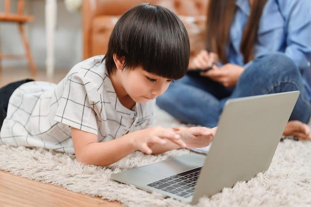Aziatische familie saamhorigheid thuis. moeder onderwijst kind voor online leeronderwijs. nieuwe normale levensstijl.