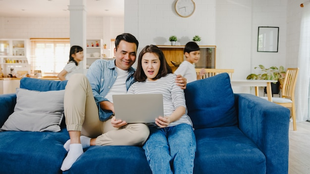 Aziatische familie vader en moeder zitten op de bank en genieten van online winkelen op laptop terwijl dochter en zoon plezier hebben terwijl ze schreeuwen rond de bank in de woonkamer thuis.