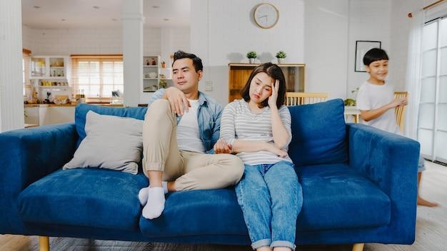 Aziatische familie vader en moeder zitten op de bank en voelen zich geïrriteerd, uitgeput terwijl dochter en zoon plezier hebben terwijl ze schreeuwen rond de bank in de woonkamer thuis.