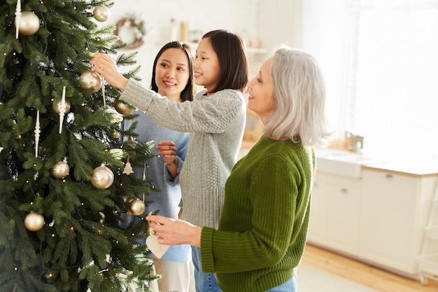 Aziatische familie van drie versieren kerstboom die samen kerstavond thuis voorbereiden