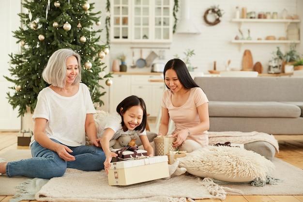 Aziatische familie van drie zittend op de vloer en kerstcadeautjes samen openen tijdens kerstavond