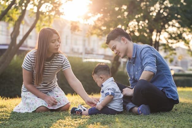 Aziatische familie zit in de tuin, mama en papa zorgen voor hun zoon op het grasveld