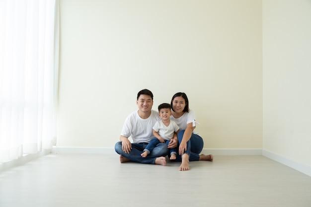 Aziatische familie zittend op de vloer in de nieuwe kamer en het nieuwe huis, verhuizing en onroerend goed concept
