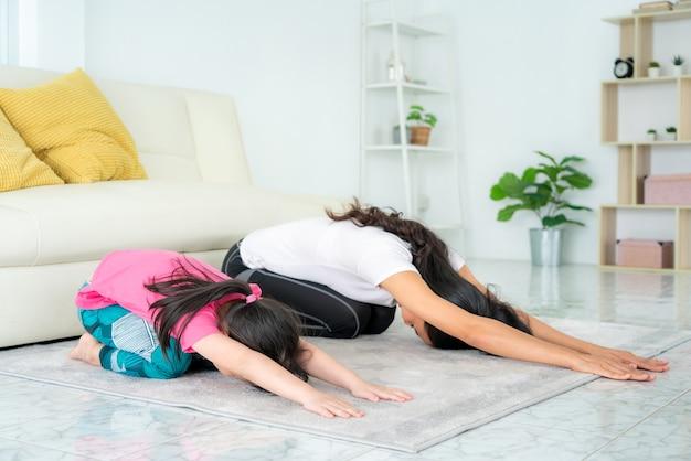 Aziatische familiemoeder en dochter die yogaoefeningen in woonkamer thuis doen