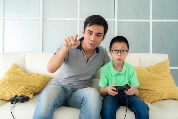 Aziatische familievader die zijn zoon onderwijst om videospelletjes te spelen