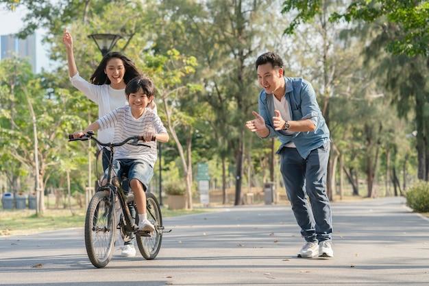 Aziatische familievader en moeder die hun zoon onderwijzen om fiets bij het park te berijden Premium Foto