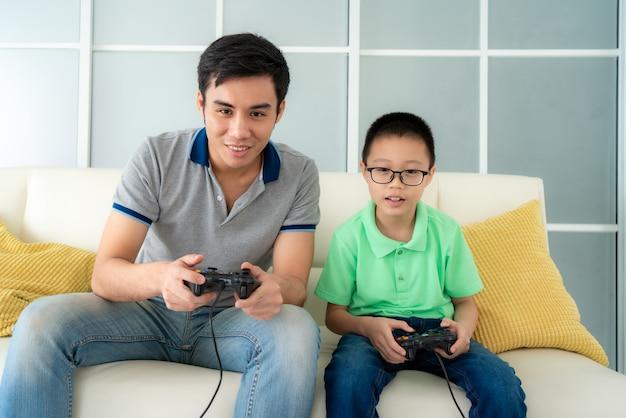 Aziatische familievader en zijn zoon om videogames te spelen