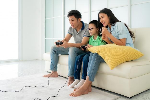Aziatische familievader en zoon die pret hebben die computerconsolespelen samen spelen