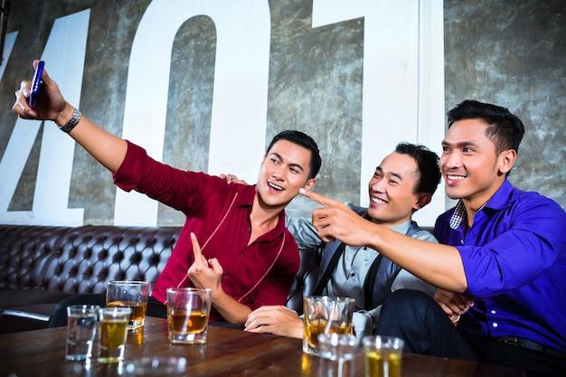 Aziatische feestvierders groep jonge vrienden die foto's of selfies maken met hun gsm of mobiele telefoon in een chique nachtclub