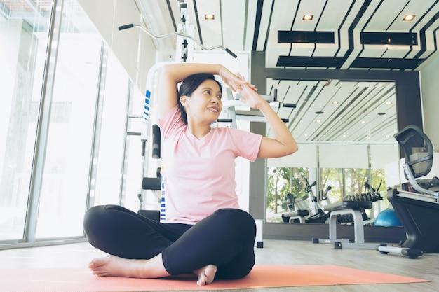 Aziatische fitness vrouw opwarmen voordat oefening in gym, middelbare leeftijd vrouw yoga uit te werken