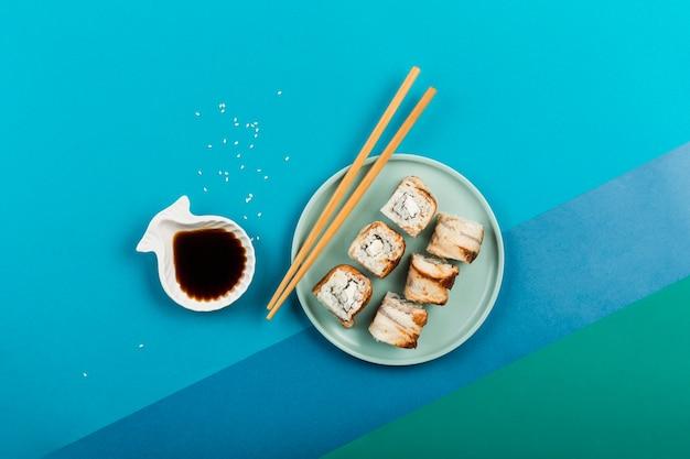 Aziatische foodeel en kaas sushi rolt op een bord met stokjes en sojasaus