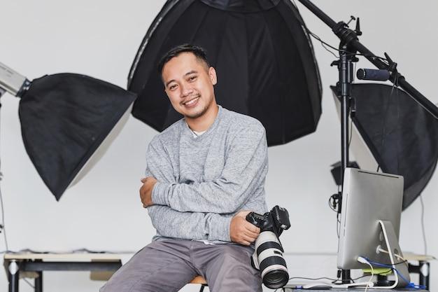 Aziatische fotograaf zit en houdt de camera vast met een zelfverzekerde glimlach