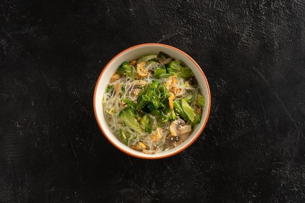 Aziatische garnituur, gekookte glasnoedels met groenten, champignons, broccoli, cashewnoten, sesamzaadjes en groene uien in een ronde plaat op een zwarte stenen tafel.