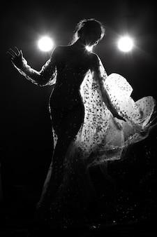 Aziatische gebruinde huid slanke sexy vrouw doorzien avondjurk met tegenlicht rook