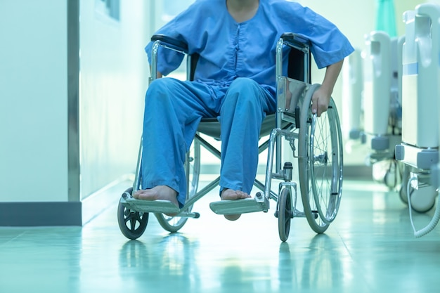 Aziatische gehandicapte man zit in een rolstoel. hij houdt zijn handen aan het stuur, medische eq