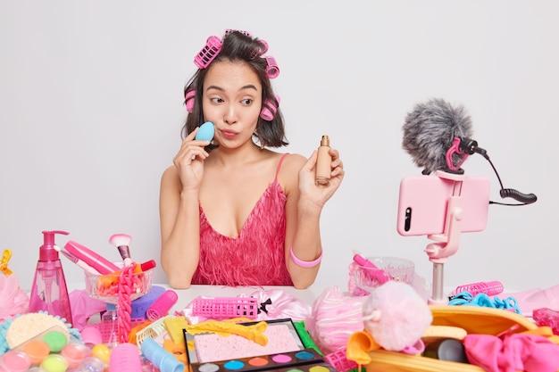 Aziatische gelaatsleraar past foundation toe met sponswerken vanuit huis registreert online make-uplessen