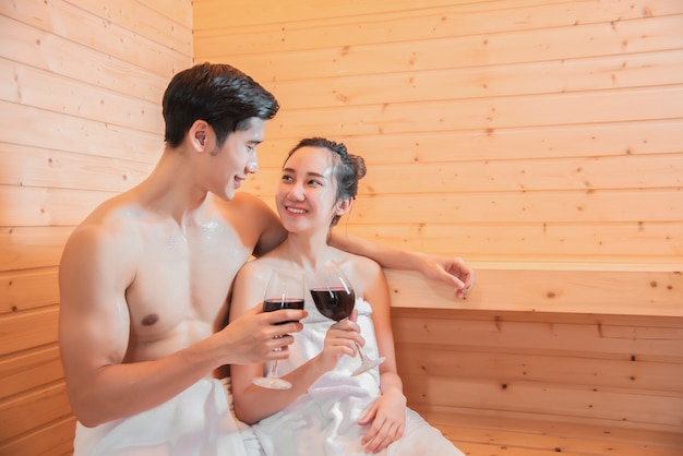 Aziatische geliefden die wijn in saunaruimte drinken