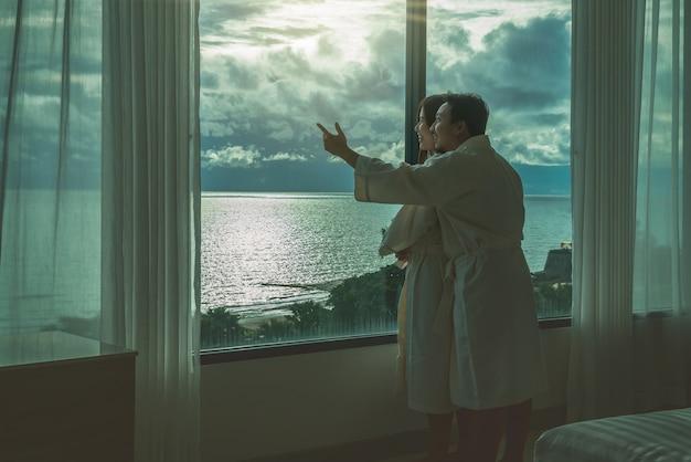Aziatische geliefden in badjaspak die en het overzeese strand koesteren bekijken wanneer het ontwaken