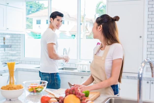 Aziatische geliefden of koppels kijken elkaar aan als ze zo grappig samen koken in de keuken
