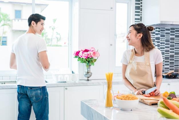 Aziatische geliefden of stellen die zo grappig samen in keuken met hoogtepunt van ingrediënt op lijst koken
