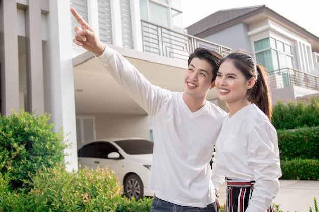 Aziatische geliefden zijn in het nieuwe huis en wijzen hun vingers naar de toekomst.