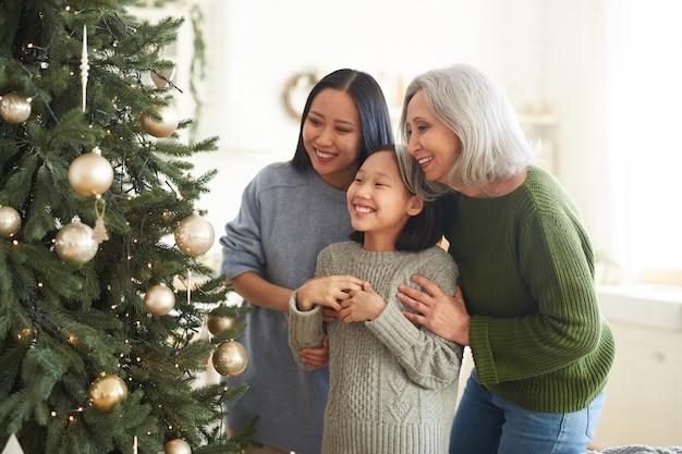 Aziatische gelukkige familie kijken naar hun versierde kerstboom in de kamer