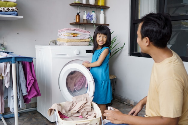 Aziatische gelukkige familie man vader gezinshoofd en kind dochter in wasgoed met wasmachine samen