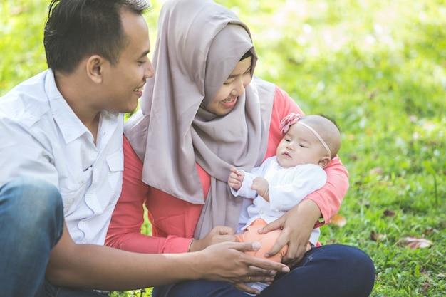 Aziatische gelukkige familie met pasgeboren baby in het park