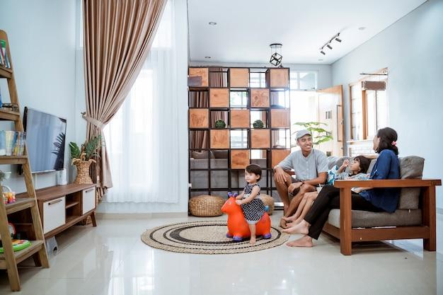 Aziatische gelukkige familie zittend op de bank thuis samen tv kijken