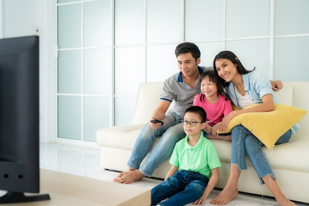 Aziatische gelukkige familiezitting in bank en thuis televisiekijken