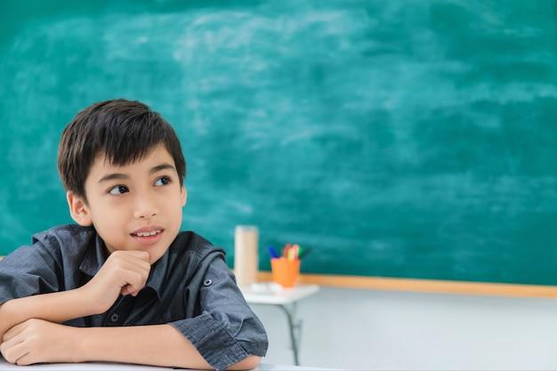 Aziatische gelukkige schooljongen die en op zwarte raad droomt denkt