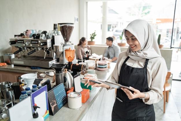 Aziatische gesluierde ober houdt een klembord