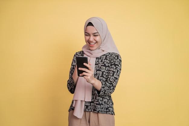 Aziatische gesluierde vrouw die naar het scherm kijkt terwijl ze een smartphone gebruikt met een vrolijke uitdrukking