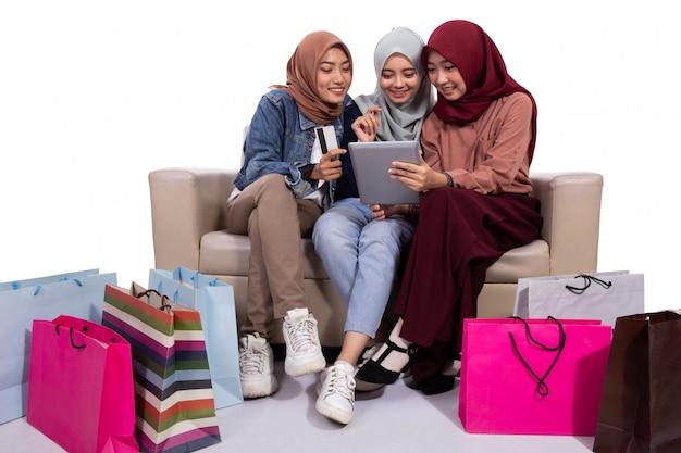 Aziatische gesluierde vrouwen die bij een online winkel kopen