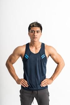 Aziatische gespierde man met sportkleding staan naar voren gericht met de handen op de taille